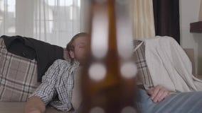 El individuo barbudo joven se cae dormido en el sofá Las bebidas alcohólicas están en la tabla antes de la cama almacen de video