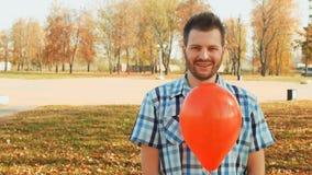 El individuo barbudo sonriente se coloca con un globo rojo en su mano almacen de metraje de vídeo