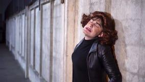 El individuo cómico vestido como mujer, la ropa negra que lleva y la peluca, canta el exterior almacen de metraje de vídeo