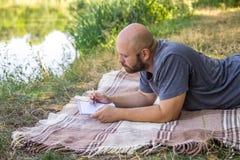 El individuo calvo escribe en un cuaderno en la hierba en una manta y piensa en los sueños cerca del sol del verano del lago Foto de archivo libre de regalías