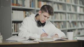 El individuo cansado se cae dormido mientras que se prepara para el examen en la biblioteca escolar almacen de metraje de vídeo