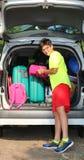 El individuo carga bolsos en el coche de equipaje Foto de archivo libre de regalías