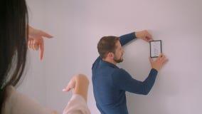 El individuo caucásico está eligiendo el lugar para la imagen enmarcada en la pared blanca mientras que su novia hace forma del m almacen de metraje de vídeo