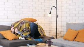 El individuo caucásico está mintiendo en el sofá debajo de la manta y jugando al juego de la consola, pierde 50 fps