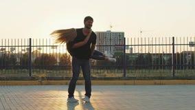 El individuo coge su novia y giros con ella Cámara lenta Pares en amor en la puesta del sol almacen de video