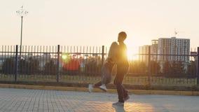 El individuo coge su novia y giros con ella Cámara lenta Pares en amor en la puesta del sol almacen de metraje de vídeo