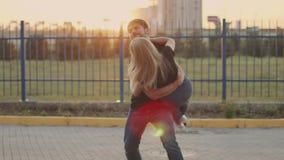 El individuo coge su novia y giros con ella Cámara lenta Pares en amor en la puesta del sol metrajes