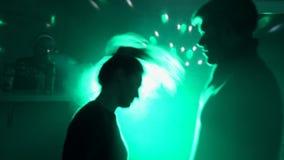El individuo con el baile de la muchacha en un disco en el club en el fondo de la luz almacen de video