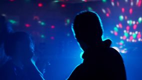 El individuo con el baile de la muchacha en un disco en el club en el fondo de la luz metrajes