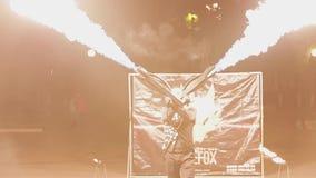 El individuo con dos lanzallamas en sus manos tira para arriba Las lenguas de la llama se alzan Demostraci?n asombrosa almacen de video