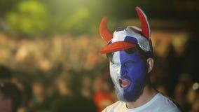El individuo con la bandera pintada del equipo de la cara se cae estadio de fútbol dormido, juego de bostezo del deporte metrajes
