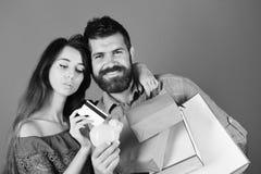 El individuo con la barba y la muchacha con las caras sonrientes hacen compras Fotos de archivo