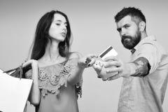 El individuo con la barba y la señora con las caras serias hacen compras Imagen de archivo libre de regalías