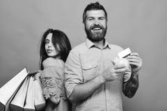 El individuo con la barba y la señora con las caras sonrientes hacen compras Fotografía de archivo
