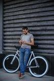 El individuo con la bici y fija el teléfono Fotografía de archivo libre de regalías