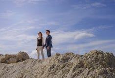 El individuo con la muchacha contra el cielo azul en la cima de la montaña imagenes de archivo