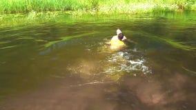 El individuo con la muchacha en el río almacen de video
