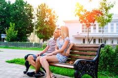 El individuo con la muchacha en un parque del verano que se sienta en resto del banco, goza de encontrar, lema feliz del concepto foto de archivo libre de regalías