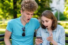 El individuo con la muchacha En verano en el parque En sus manos sostiene un smartphone Emociones de la sorpresa Una sorpresa fel Fotografía de archivo libre de regalías