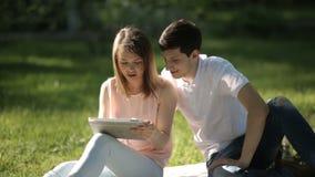 El individuo con la muchacha que se sienta en el parque y que mira la tableta metrajes