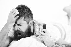 El individuo con la mueca soñolienta en cara miente en la almohada, despertador de los controles El hombre sufre por la mañana, f imagenes de archivo