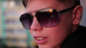 El individuo con las gafas de sol está mirando la puesta del sol Los rayos del ` s del sol se reflejan en el vidrio almacen de metraje de vídeo