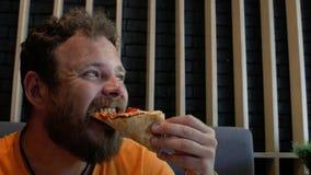 El individuo con las mordeduras pizza caliente y ceños fruncidos de la barba 4K v?deo 4K metrajes