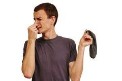 El individuo con los calcetines sucios en sus manos en un fondo blanco fotos de archivo