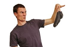 El individuo con los calcetines sucios en sus manos en un fondo blanco fotografía de archivo