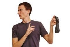 El individuo con los calcetines sucios en sus manos en un fondo blanco imagen de archivo