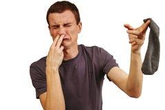 El individuo con los calcetines sucios en sus manos en un fondo blanco imagen de archivo libre de regalías