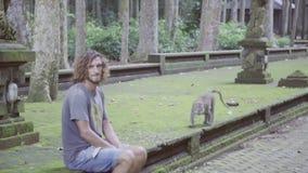 El individuo con el pelo rizado largo en camiseta y pantalones cortos se sienta en monos de observación del encintado metrajes