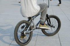 El individuo con ropa de los deportes se sienta en la bicicleta de los deportes BMX Imagen de archivo