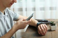 El individuo con un reloj elegante y un smartphone Imagen de archivo