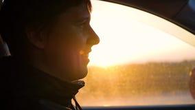 El individuo conduce el coche en un día soleado Tiempo de la puesta del sol almacen de video