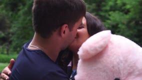 El individuo da a su muchacha querida un oso de peluche y la besa almacen de metraje de vídeo