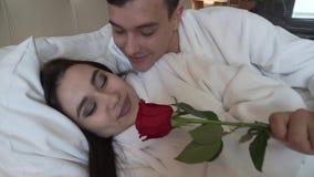 El individuo da su rosa del rojo de la muchacha el dormir y besan el vídeo común de la cantidad metrajes