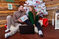 El individuo da un regalo a una muchacha que se sienta en una manta en el fondo de un árbol de navidad Fotos de archivo libres de regalías