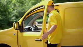 El individuo de la entrega en uniforme amarillo da el paquete al cliente femenino cerca del coche metrajes