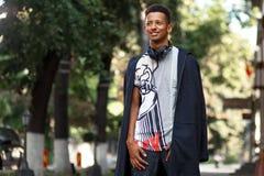 El individuo de la raza mixta afuera, llevando en ropa y auriculares modernos, tiene buen d?a, fondo borroso aislado fotografía de archivo