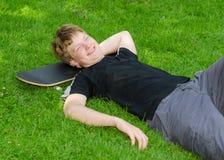 El individuo de risa se relaja en el monopatín en hierba del parque Foto de archivo