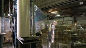 El individuo de Warehouse con la envoltura automática envuelve los tarros y las cajas de cristal de la película de estiramiento e almacen de video