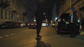 El individuo del skater en sudadera con capucha negra monta en avenida de la ciudad de la noche almacen de metraje de vídeo