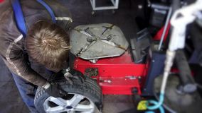 El individuo del trabajador desmonta el neumático de la rueda metrajes
