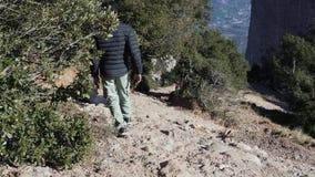 El individuo desciende una cuesta escarpada de una montaña almacen de metraje de vídeo