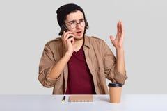 El individuo descontentado emocional tiene conversación telefónica, aumenta la mano, discute algo activamente, bebe el café para  foto de archivo libre de regalías