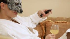 El individuo descontentado en máscara del lobo mira la TV metrajes