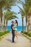 El individuo detiene a la muchacha en las manos en una playa con las palmeras Foto de archivo libre de regalías