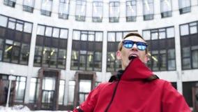 El individuo dinámico en equipo y gafas de sol rojos del deporte canta al lado de columnas del granito almacen de metraje de vídeo
