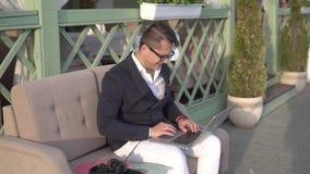 El individuo divertido escribe rápidamente en el ordenador portátil metrajes